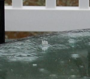 A rain drop hitting a glass table top