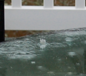 A rain drop hitting a glass table top